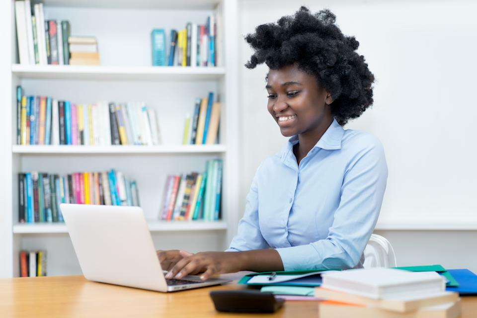 Beautiful african american student or business trainee working at computer at desk at office
