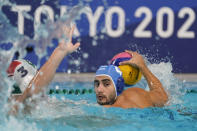 Greece's Marios Kapotsis (4) looks for a teammate past Hungary's Krisztian Manhercz (3) during a preliminary round men's water polo match at the 2020 Summer Olympics, Sunday, July 25, 2021, in Tokyo, Japan. (AP Photo/Mark Humphrey)