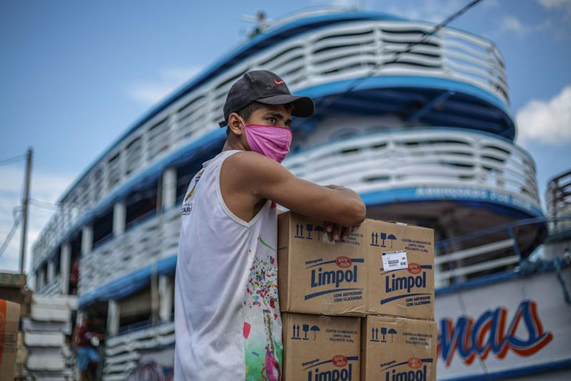 A man sits with cardboard boxes in front of a boat at Manaus port. Source: Getty Images
