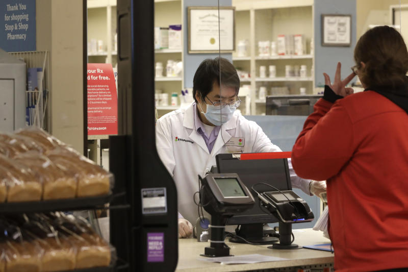 A pharmacist, left, assists a customer while working behind a plastic shield at a grocery store, Thursday, March 26, 2020, in Quincy, Mass. Grocery stores across the U.S. are installing protective plastic shields at checkouts to help keep cashiers and shoppers from infecting each other with the coronavirus. (AP Photo/Steven Senne)