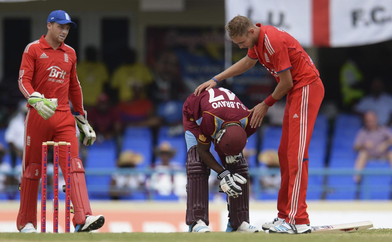 England's Stuart Broad (R) and team mate Jos Buttler (L) check on West Indies' captain Dwayne Bravo after he was struck by a bouncer during the second one-day international cricket match at North Sound, Antigua March 2, 2014. REUTERS/Philip Brown (ANTIGUA - Tags: SPORT CRICKET)