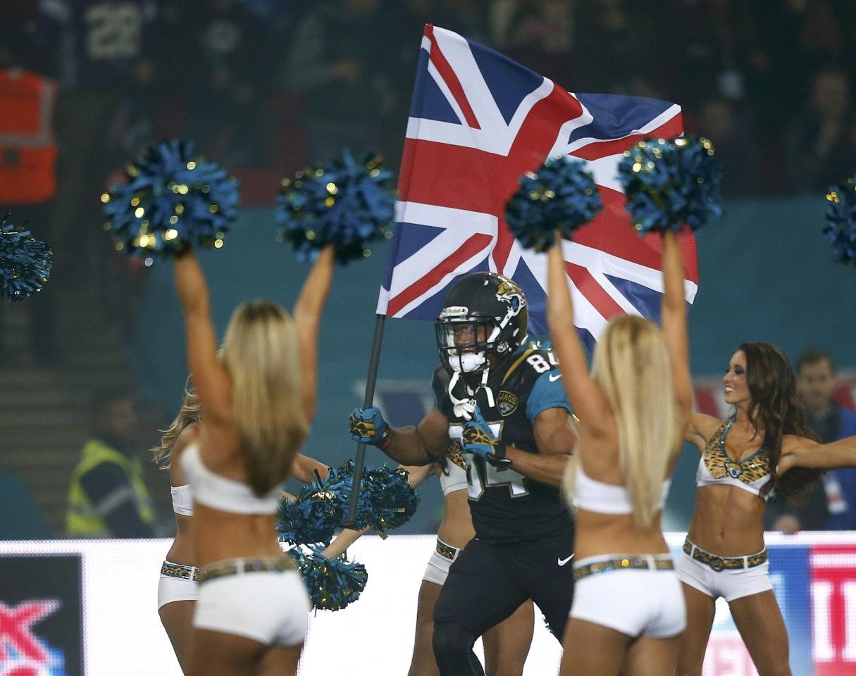 Jacksonville Jaguars wide receiver Cecil Shorts carries Britain's Union Jack past Jaguars' cheerleaders as he enters the field before the Jaguars met the San Francisco 49ers during their NFL football game at Wembley Stadium in London, October 27, 2013. REUTERS/Andrew Winning (BRITAIN - Tags: SPORT FOOTBALL)