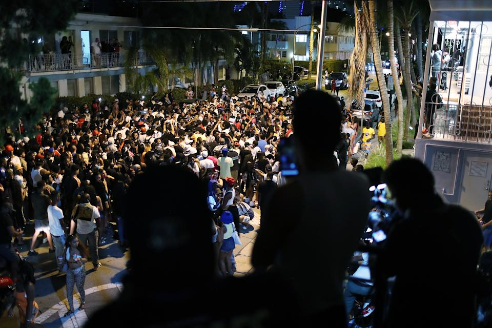 MIAMI BEACH, FLORIDA - MARCH 21: People gather while exiting the area as an 8pm curfew goes into effect on March 21, 2021 in Miami Beach, Florida. College students have arrived in the South Florida area for the annual spring break ritual, prompting city officials to impose an 8pm to 6am curfew as the coronavirus pandemic continues. Miami Beach police have reported hundreds of arrests and stepped up deployment to control the growing spring break crowds. (Photo by Joe Raedle/Getty Images)