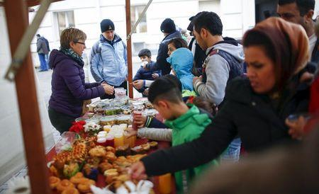 Migrants receive food at a Christmas market at a refugee shelter run by German charity organisation Arbeiter Samariter Bund ASB in Berlin, Germany, December 12, 2015. REUTERS/Hannibal Hanschke