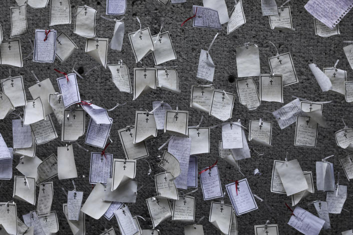Messages written by loved ones and dedicated to the deceased hang from a wall at a memorial for COVID-19 victims installed outside the Basilica of Guadalupe in Mexico City, Wednesday, April 14, 2021. (AP Photo/Eduardo Verdugo)