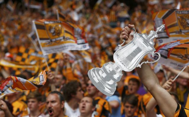 A Hull City supporter holds a cardboard replica of the FA cup before the start of his team's FA Cup final soccer match against Arsenal at Wembley Stadium in London, May 17, 2014. REUTERS/Eddie Keogh (BRITAIN - Tags: SPORT SOCCER)