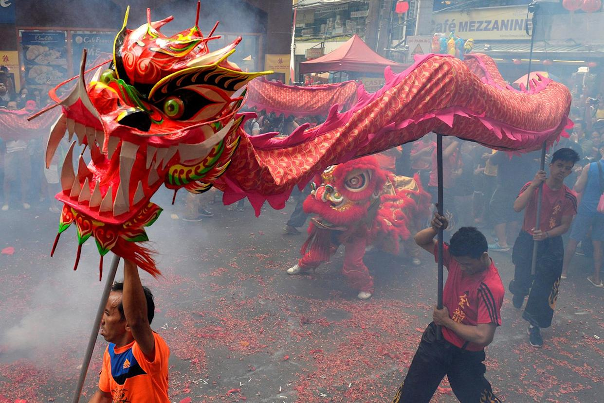 Revellers perform a dragon dance among smoke caused by firecrackers during Chinese Lunar New Year celebrations in Manila's Chinatown, Philippines January 28, 2017. (REUTERS/Ezra Acayan)