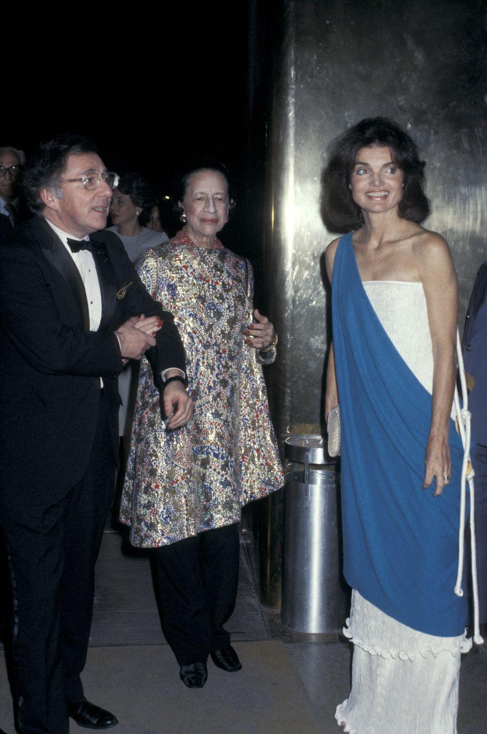 <p>Carl Katz, Diana Vreeland, and Jackie Onassis are photographed at the Metropolitan Museum of Art, with Jackie wearing a strapless white gown with a blue overlay. <br></p>