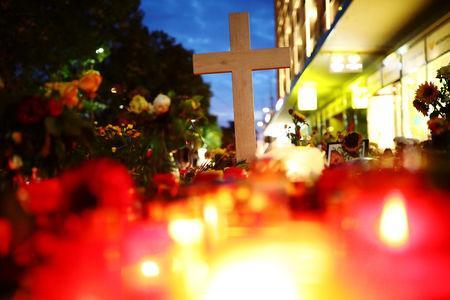A cross, candles and flowers are seen at the crime scene where a German man was stabbed in Chemnitz, Germany, August 31, 2018. REUTERS/Hannibal Hanschke