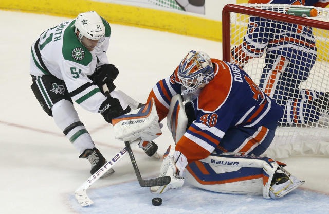 Edmonton Oilers goalie Devan Dubnyk (40), of Canada, blocks a shot by Dallas Stars right wing Austin Smith (51) in the first period of an NHL preseason hockey game in Oklahoma City, Friday, Sept. 27, 2013. (AP Photo/Sue Ogrocki)