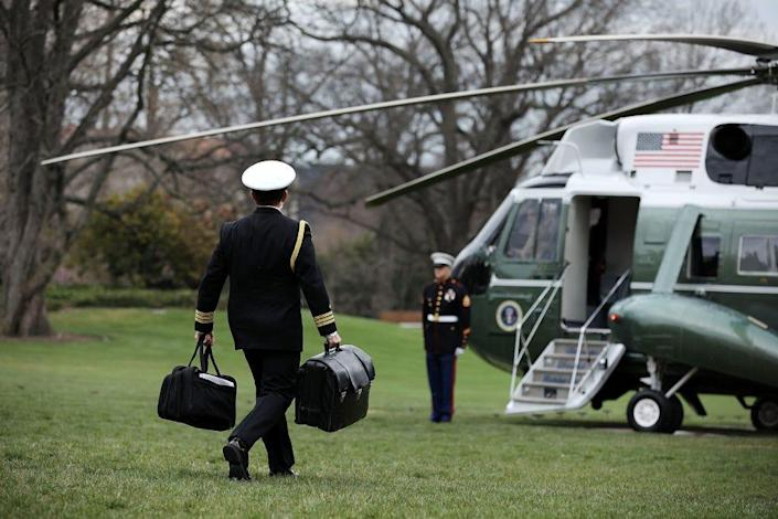 "A White House military aide carries the nuclear ""football"" as he leaves the White House"