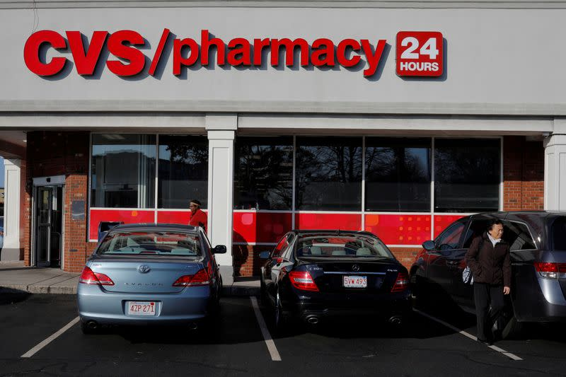 FILE PHOTO: Shoppers walk outside a CVS store and pharmacy in Medford
