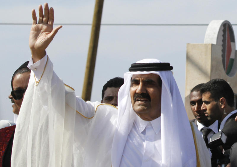FILE- In this Tuesday, Oct. 23, 2012 file photo, Emir of Qatar Sheikh Hamad bin Khalifa al-Thani waves to the crowd as he and and Gaza's Hamas Prime Minister Ismail Haniyeh, not pictured, arrive for corner-stone laying ceremony of a Qatari funded rehabilitation center in Gaza City. (AP Photo/Hatem Moussa, Pool, File)