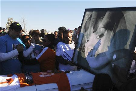 Family members and friends stand next to a coffin holding the remains of Idaly Jauche Laguna in Ciudad Juarez December 27, 2013. REUTERS/Jose Luis Gonzalez