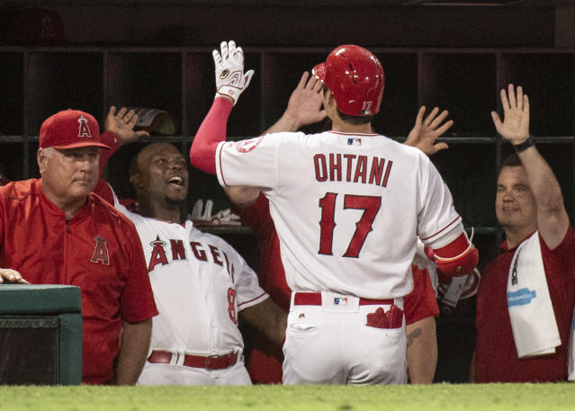 The Los Angeles Angels dugout welcomes Shohei Ohtani after he hit a solo home run during the fourth inning of a baseball game against the Chicago White Sox in Anaheim, Calif., Monday, July 23, 2018. (AP Photo/Kyusung Gong)