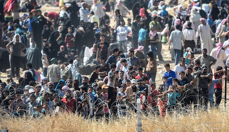 Syrians fleeing fighting in the city centre of the Syrian town of Tal Abyad ask for water as they gather at a border crossing on the Syrian side of the border with Turkey (AFP Photo/Bulent Kilic)