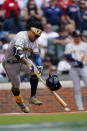 Milwaukee Brewers second baseman Kolten Wong (16) loses his helmet as he grounds out during the first inning of Game 3 of a baseball National League Division Series against the Atlanta Braves, Monday, Oct. 11, 2021, in Atlanta. (AP Photo/John Bazemore)