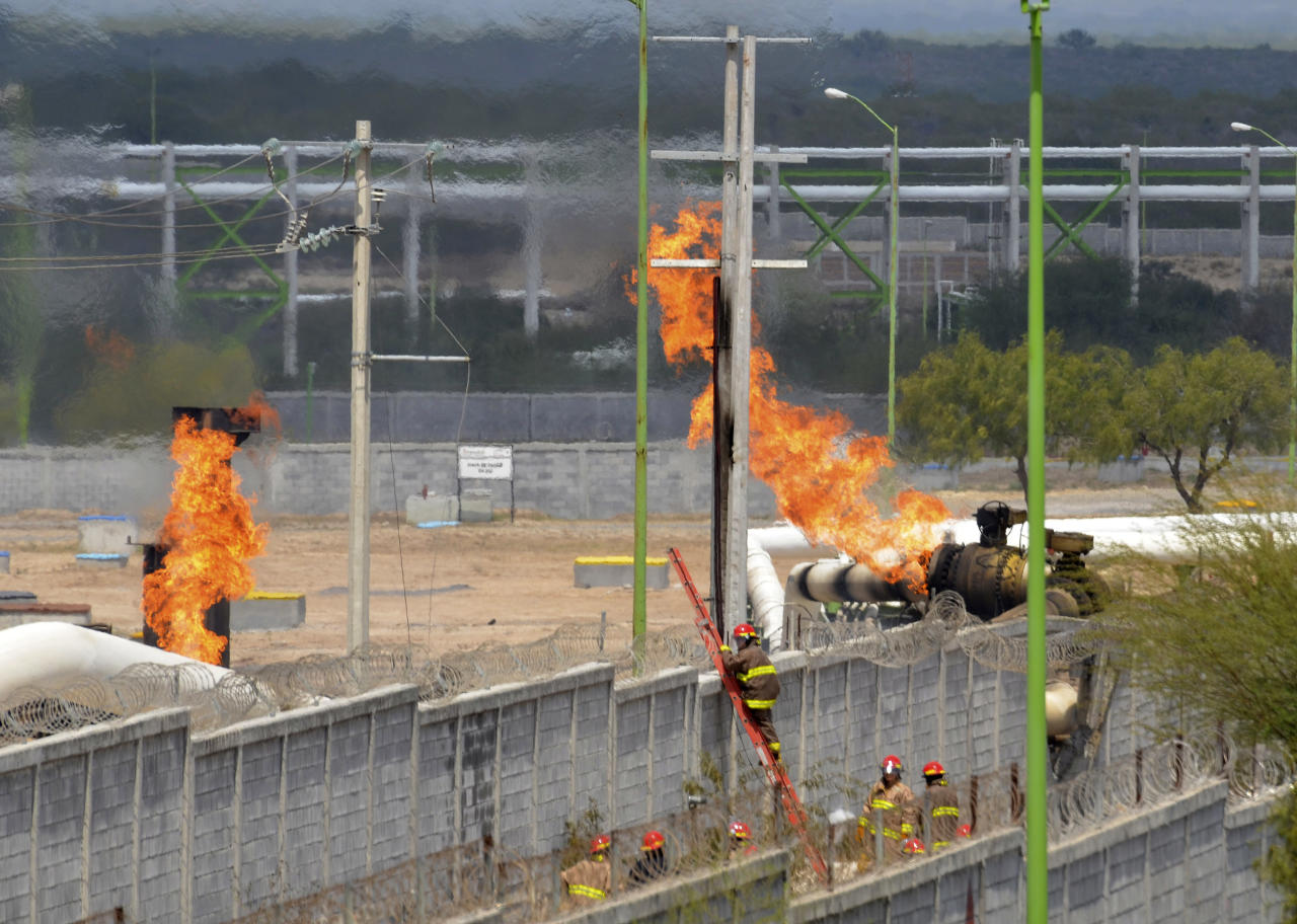Firefighter climb a ladder as they try to control a fire after an explosion at a gas pipeline distribution center in Reynosa, Mexico near Mexico's border with the United States, Tuesday Sept. 18, 2012. (AP Photo/El Manana de Reynosa)