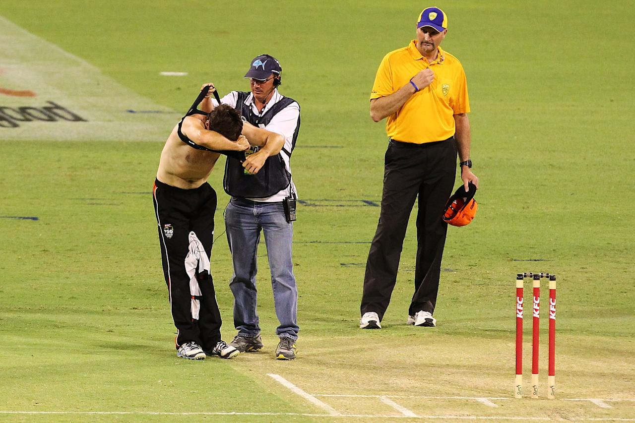 PERTH, AUSTRALIA - DECEMBER 09: Brad Hogg has his radio communications vest removed by a Fox technician during the game during the Big Bash League match between the Perth Scorchers and Adelaide Strikers at WACA on December 9, 2012 in Perth, Australia.  (Photo by Will Russell/Getty Images)