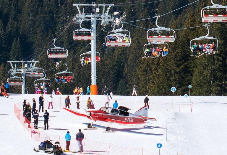 People gather around an airplane after it made an emergency landing on a ski slope in the French Alpine ski resort of Avoriaz, March 12, 2015