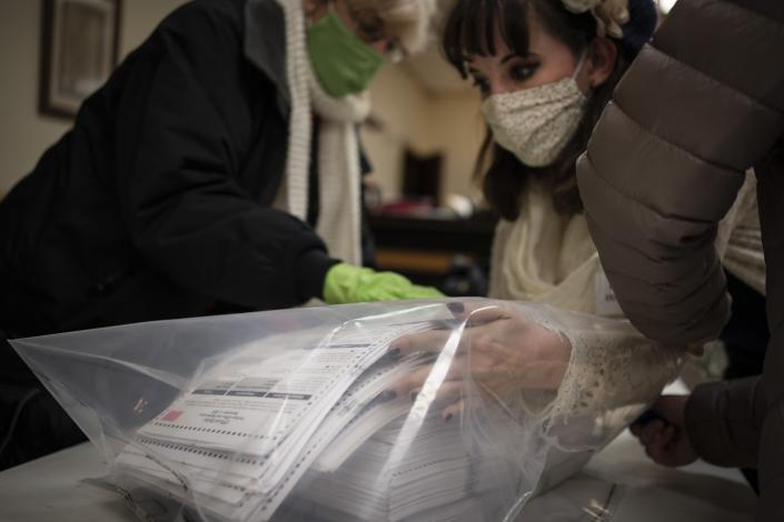 "In this Nov. 3, 2020, photo, election staff members pack ballots after polls closed at the Moose Lodge on Election Day in Kenosha, Wis. President-elect Joe Biden shored up the Democrats' ""blue wall,"" — more sturdily in Michigan, more tenuously in Pennsylvania and Wisconsin — to rebuild the party's path back to the White House. (AP Photo/Wong Maye-E, File)"