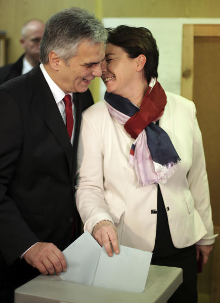 Top candidate of the Social Democrats, SPOE, Werner Faymann, left, kisses his wife Martina Ludwig-Faymann as they cast their votes in national elections at a polling station in Vienna, Austria, Sunday, Sept. 29, 2013. Austrians went to the polls to elect a new parliament. (AP Photo/Matthias Schrader)