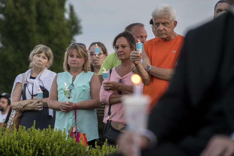 People hold candles during a prayer and candlelight vigil for four missing men who was killed and whose remains buried on a farm, at the Garden of Reflection in Lower Makefield, Pa., Sunday, July 16, 2017. Police found the four missing men's remains on a farm in Solebury Township, Pa., last week. The farm owners' son and his cousin have been charged in the slayings. (Clem Murray/The Philadelphia Inquirer via AP)