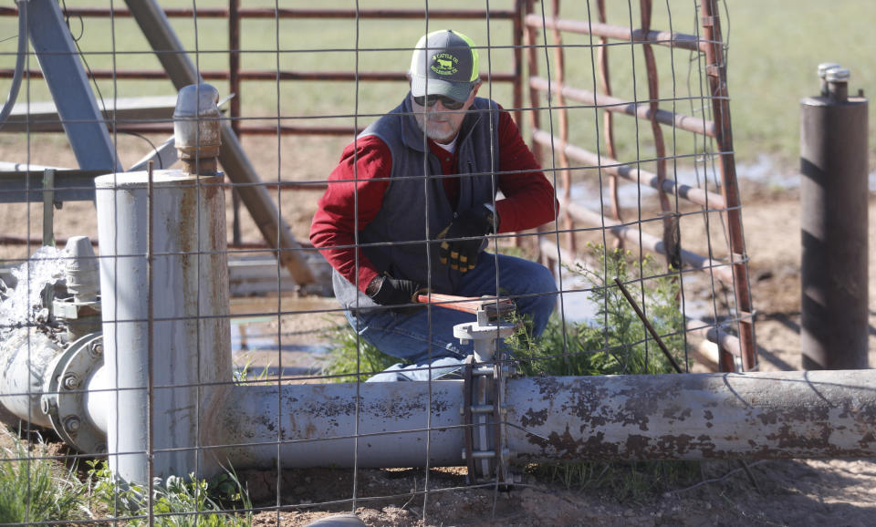 Tim Black closes a valve while swapping water from one pivot to another on his Muleshoe, Texas, farm on Monday, April 19, 2021. The longtime corn farmer now raises cattle and plants some of his pasture in wheat and native grass – and rations water use -- because the Ogallala Aquifer is drying up. (AP Photo/Mark Rogers)