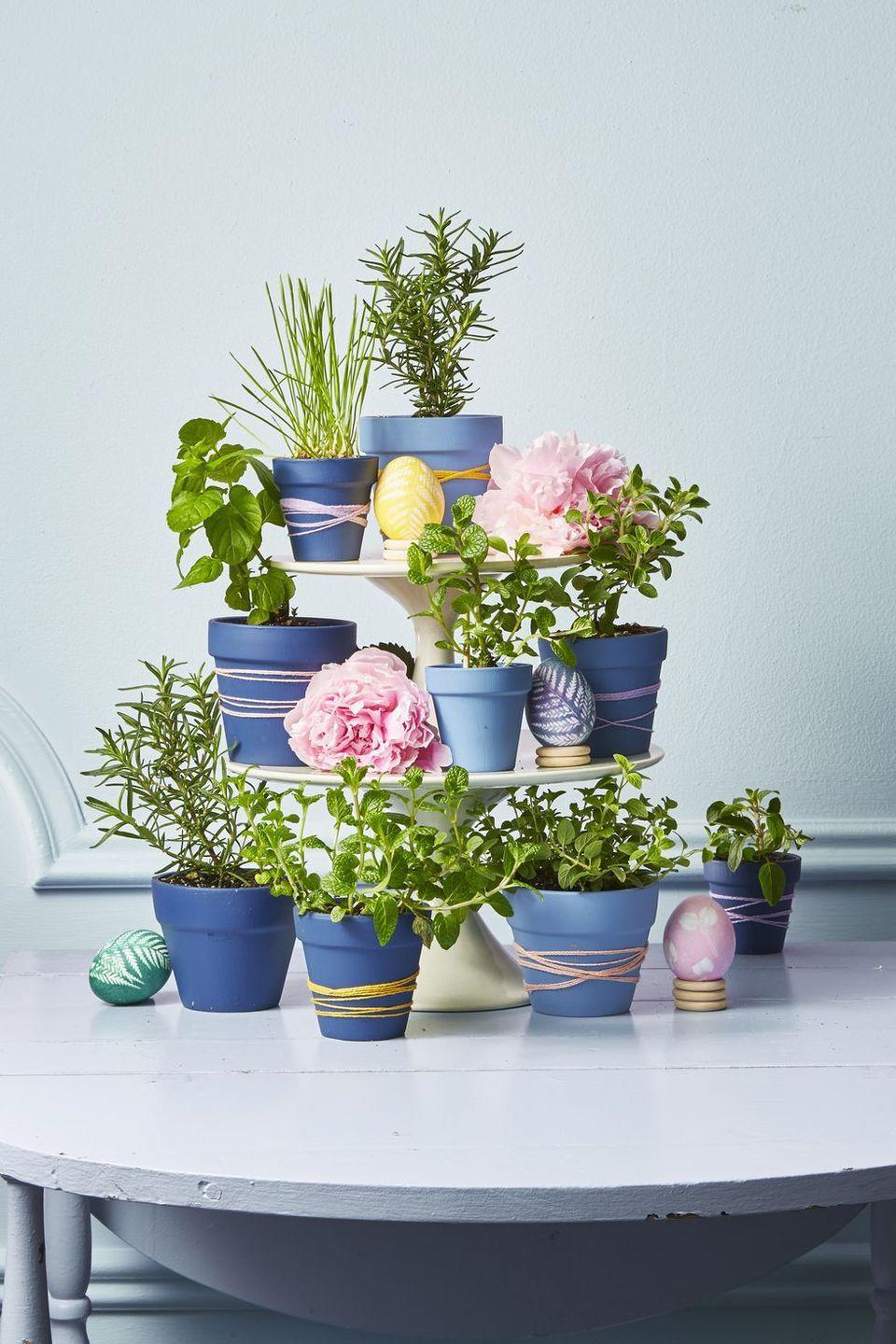 """<p>Why have one flower vase for your Easter spread when you can have a dozen? Transfer plants — succulents, greens, or fresh blooms — into painted pots wrapped in embroidery thread. Arrange the pots on stacked cake stands for a standout table topper.</p><p><a class=""""link rapid-noclick-resp"""" href=""""https://www.amazon.com/My-Urban-Crafts-Small-Terra/dp/B0798C98X7/?tag=syn-yahoo-20&ascsubtag=%5Bartid%7C10055.g.2217%5Bsrc%7Cyahoo-us"""" rel=""""nofollow noopener"""" target=""""_blank"""" data-ylk=""""slk:BUY POTS"""">BUY POTS</a> </p>"""