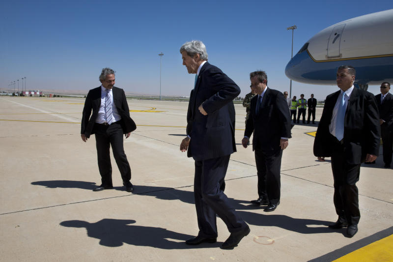 U.S. Secretary of State John Kerry, center, arrives in Amman, Jordan on Wednesday, March 26, 2014. Kerry arrived in Jordan in hopes of jump-starting foundering Mideast peace talks just as Arab leaders released a communique saying they will never recognize Israel as a Jewish state. (AP Photo/Jacquelyn Martin, Pool)