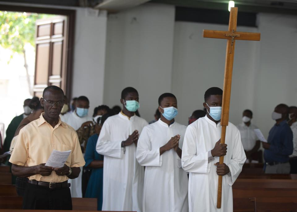 Altar boys carry a cross while wearing face masks to curb the spread of the new coronavirus, during Sunday Mass at St-Louis church, in Port-au-Prince, Sunday, July 11, 2021, four days after President Jovenel Moise was assassinated in his home. (AP Photo/Joseph Odelyn)