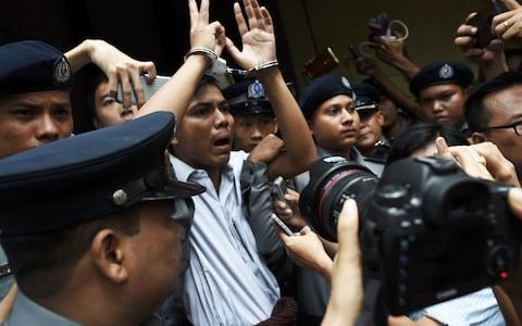 Burmese journalist Kyaw Soe Oo is escorted by police after being sentenced by a court to jail in Yangon - Credit: AFP