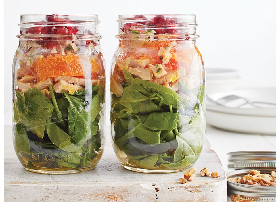 mason jar salad with spinach, turkey, cara cara oranges, and pomegranate seeds on wooden tray with jar of nuts and white plate