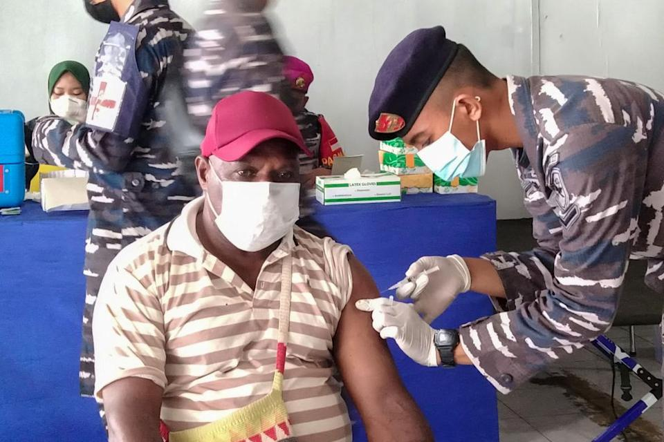 A Papuan man receives a dose of the Sinovac Covid-19 coronavirus vaccine conducted by Indonesian navy medical team at Sorong seaport, in Sorong, West Papua.
