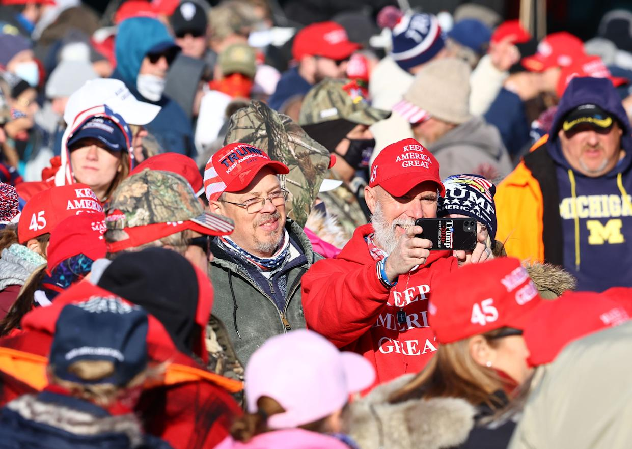 People wait for President Donald Trump to arrive at a campaign rally on November 2, 2020 in Traverse City, Michigan.