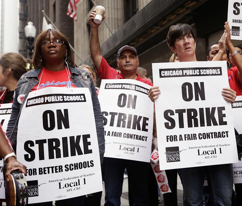 Chicago Teachers Union members listen to an update about negotiations on the fourth day of their strike on Sept. 13, 2012.