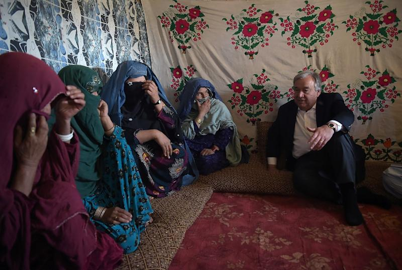 UN Secretary General Antonio Guterres (R) talks with Afghan women who fled conflict at a camp for internally displaced persons (IDP) on the outskirts of Kabul on June 14, 2017