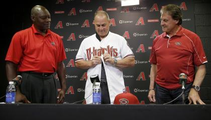 Chip Hale, middle, puts on a Diamondbacks jersey as he is introduced by Dave Stewart and Tony LaRussa. (AP)