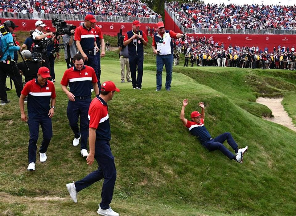 A jubilant Xander Schauffele slides down an embankment hill on his way to the podium after Team USA's Ryder Cup win (Anthony Behar/PA) (PA Wire)