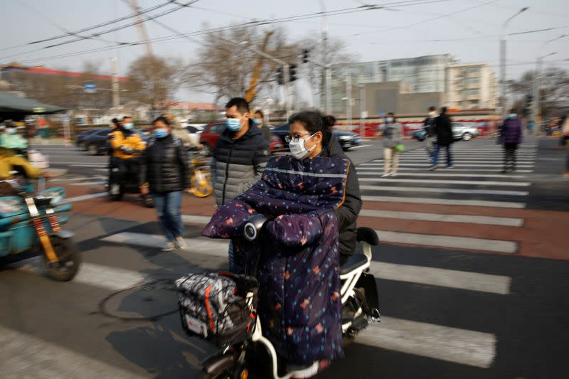 People wearing face masks ride scooters and walk on a street following an outbreak of the coronavirus disease (COVID-19), in Beijing, China