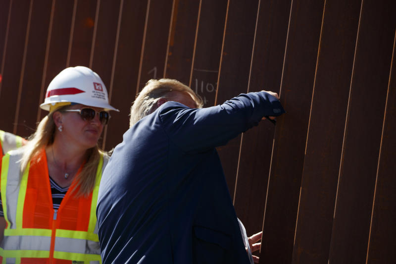 President Donald Trump signs his name as he tours a section of the southern border wall, Wednesday, Sept. 18, 2019, in Otay Mesa, Calif. (AP Photo/Evan Vucci)