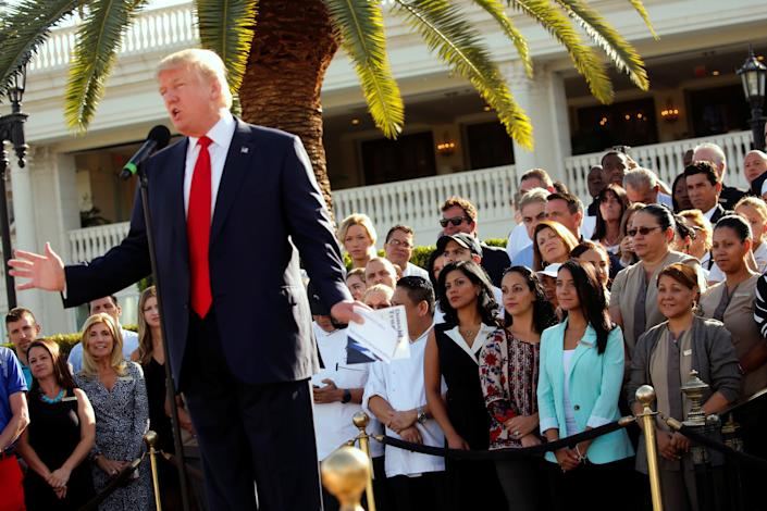 Employees of then-GOP presidential nominee Donald Trump stand behind him at a campaign event at his Trump National Doral golf club in Miami on Oct. 25, 2016. (Photo: Jonathan Ernst / Reuters)