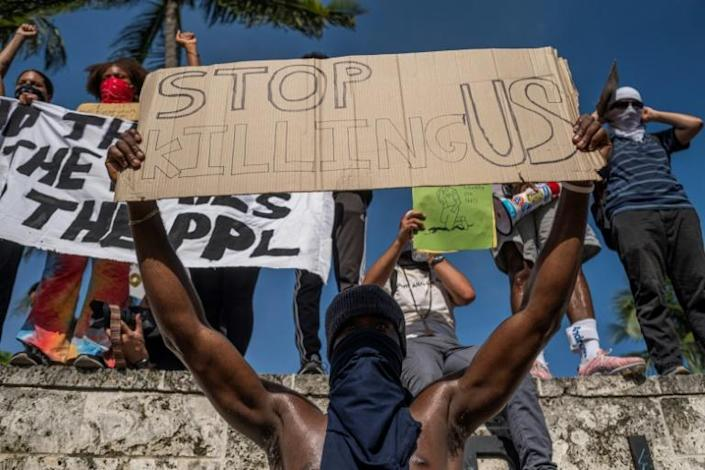 Protesters hold signs during a rally on May 31 in Miami in response to the death of George Floyd, an unarmed black man who died while in police custody in Minneapolis (AFP Photo/Ricardo ARDUENGO)