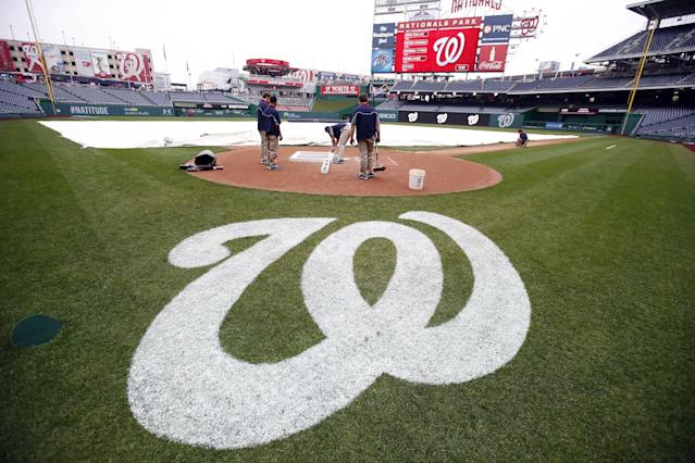 The grounds crew readies the field before an exhibition baseball game between the Washington Nationals and the Detroit Tigers at Nationals Park Saturday, March 29, 2014, in Washington. (AP Photo/Alex Brandon)