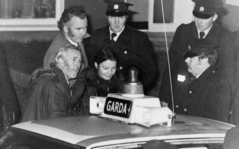 Marian Coyle is escorted to a police car after she and Eddie Gallagher had surrendered - Bettmann