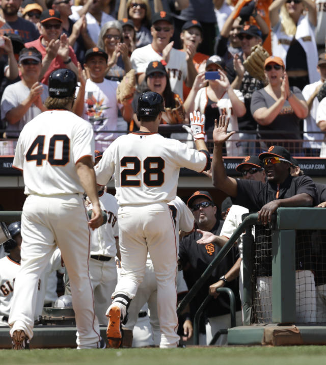 San Francisco Giants' Buster Posey (28) is congratulated upon returning to the dugout after hitting a grand slam off Arizona Diamondbacks' Vidal Nuno in the fifth inning of a baseball game Sunday, July 13, 2014, in San Francisco. (AP Photo/Ben Margot)