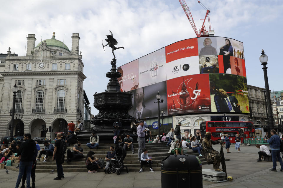 People sit and stand around the Anteros statue by the big advertising screens in the Piccadilly Circus area of central London, Saturday, Sept. 19, 2020. Fresh nationwide lockdown restrictions in England appear to be on the cards soon as the British government targeted more areas Friday in an attempt to suppress a sharp spike in new coronavirus infections. (AP Photo/Matt Dunham)