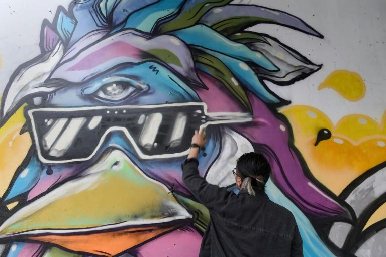 Dan Nguyen works on his graffiti in Vietnam's Ho Chi Minh City, which has become a street art hub