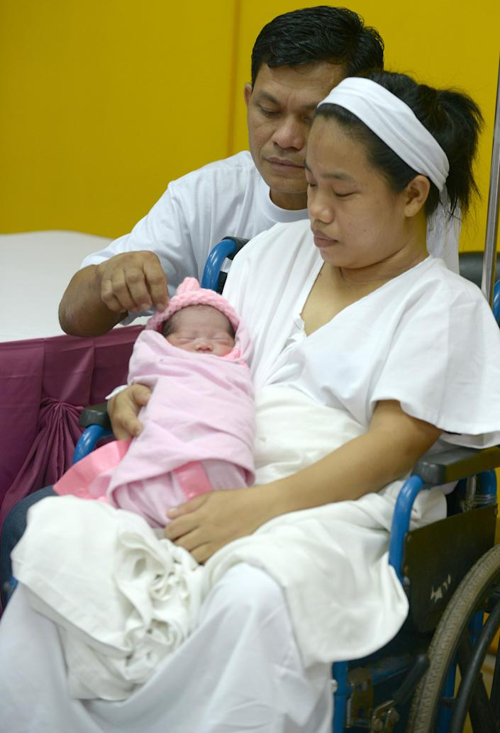 """Newly-born baby girl Jennalyn Sentino, the Philippines' """"100,000,000th baby"""", with mother Dailin Cabigayan and father Clemente Sentino during a presentation at a government hospital in Manila on July 27, 2014 (AFP Photo/Jay Directo)"""