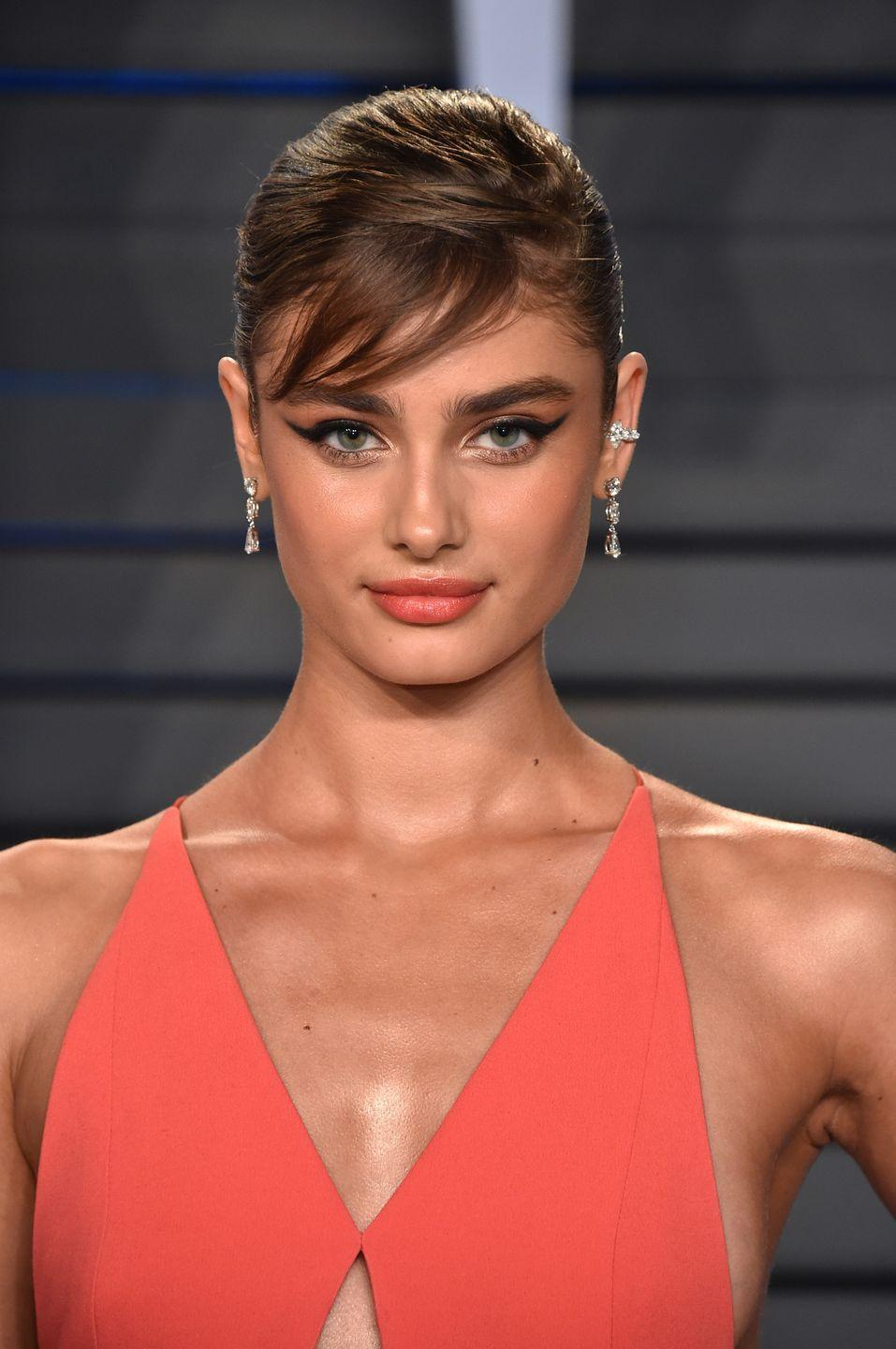 <p>Brushed to one side, Taylor Hill's Audrey Hepburn-esque side bangs are an unexpected accent to her electric coral gown and lipstick.</p>